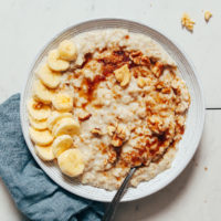 Bowl of Instant Pot oats topped with sliced banana, brown sugar, and pecans