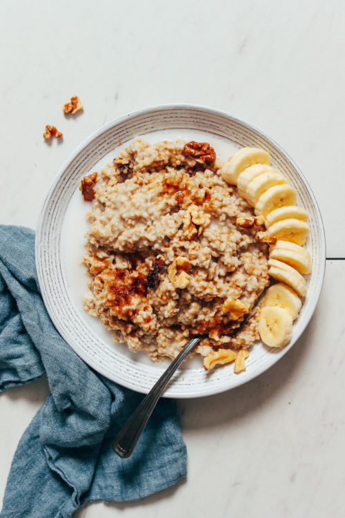 Bowl of steel cut oats with sliced banana, walnuts, and brown sugar