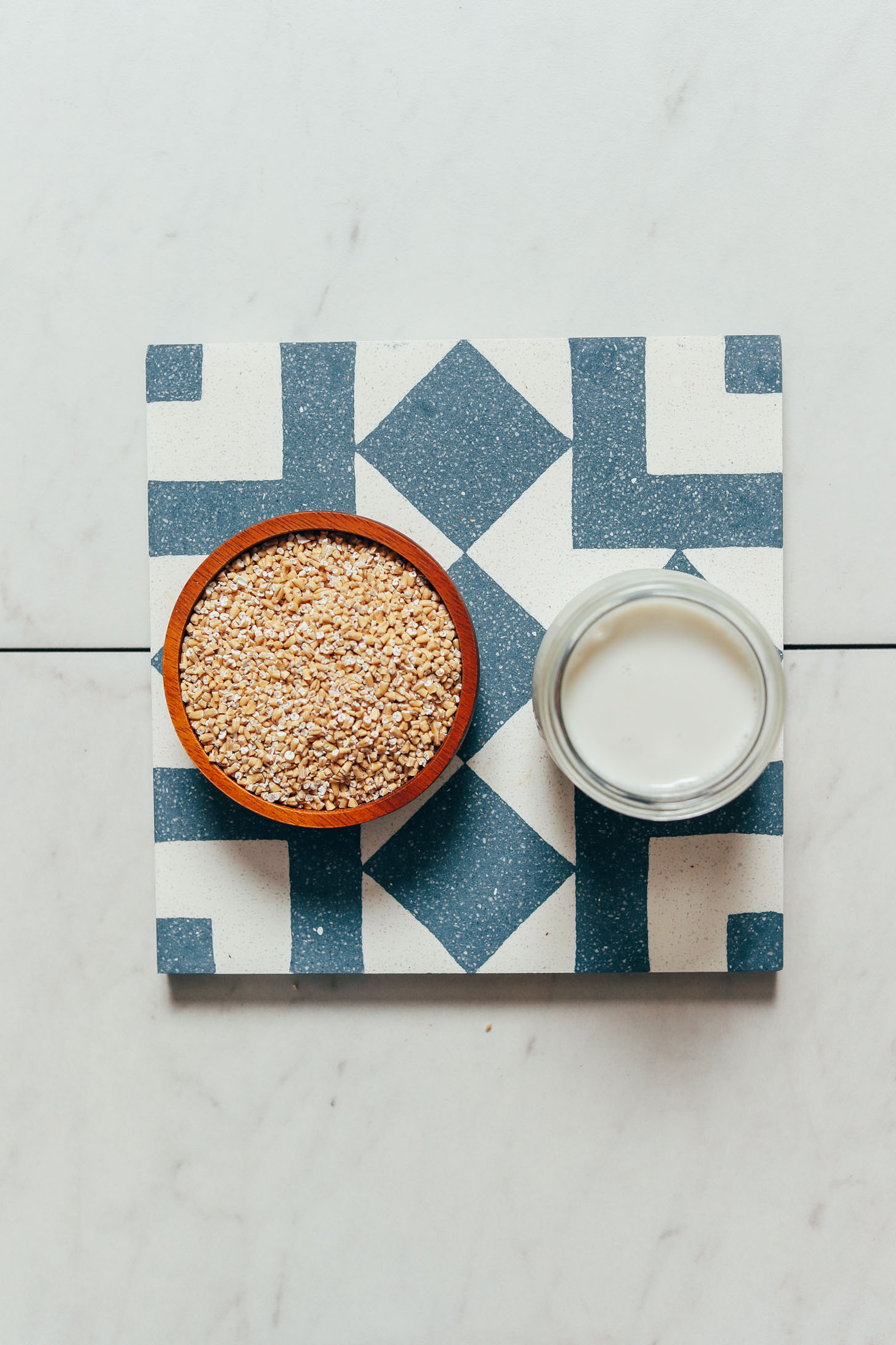 Bowl of steel cut oats and jar of dairy-free milk