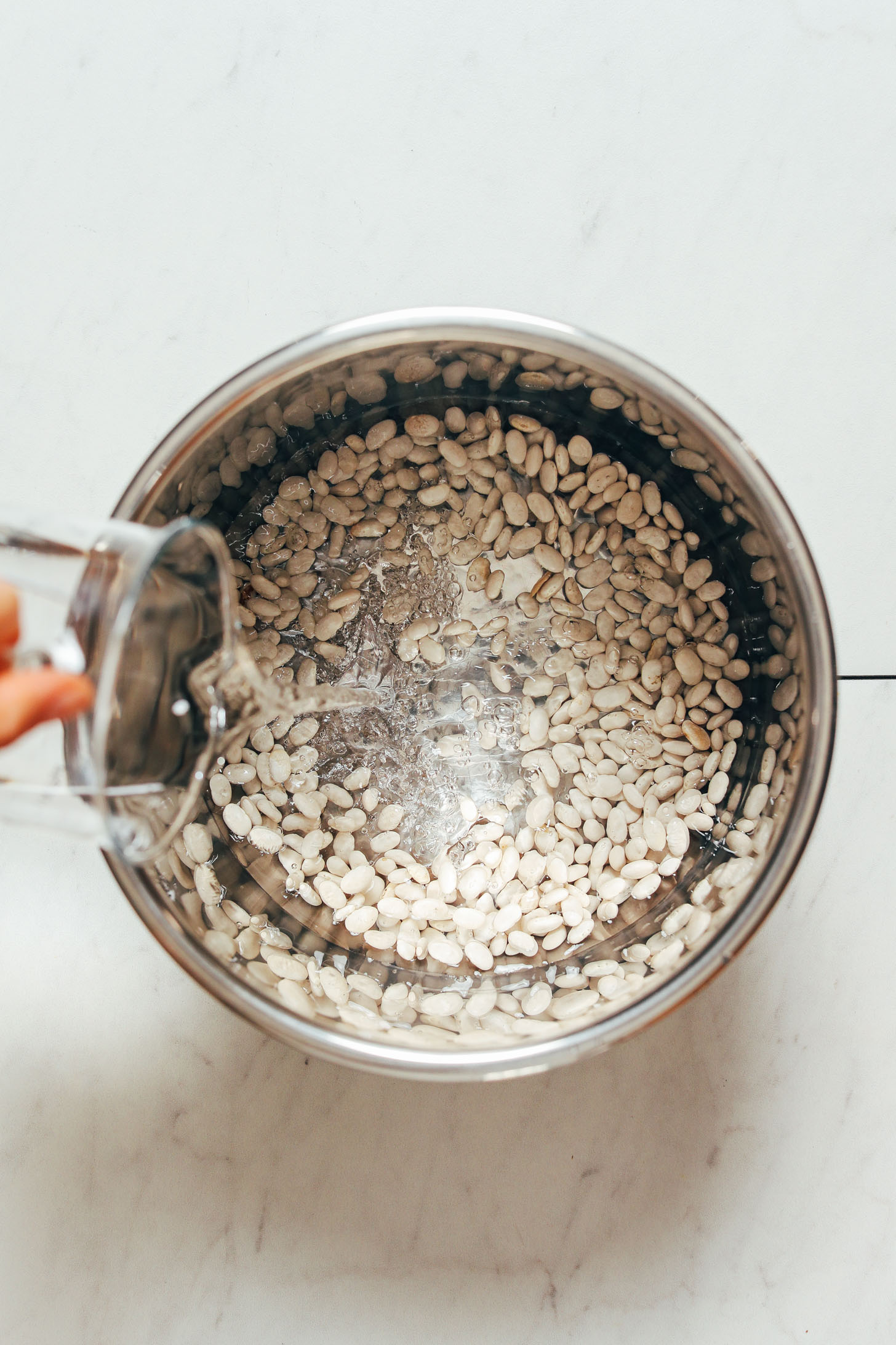 Pouring water over Great Northern Beans in an Instant Pot