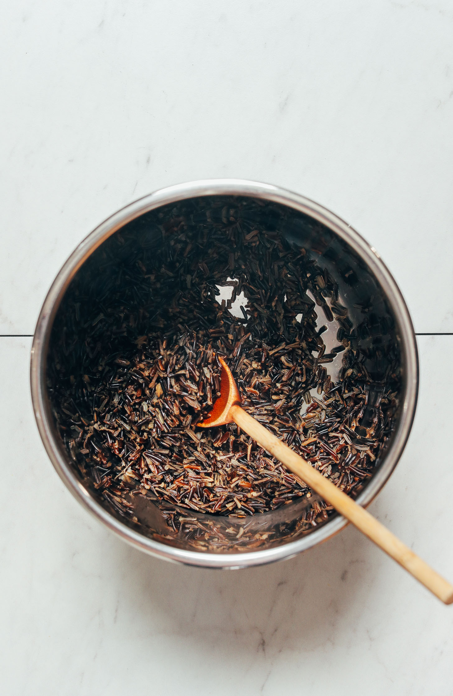 Wooden spoon in an Instant Pot of wild rice