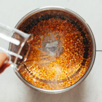 Pouring water into an Instant Pot of yellow split peas
