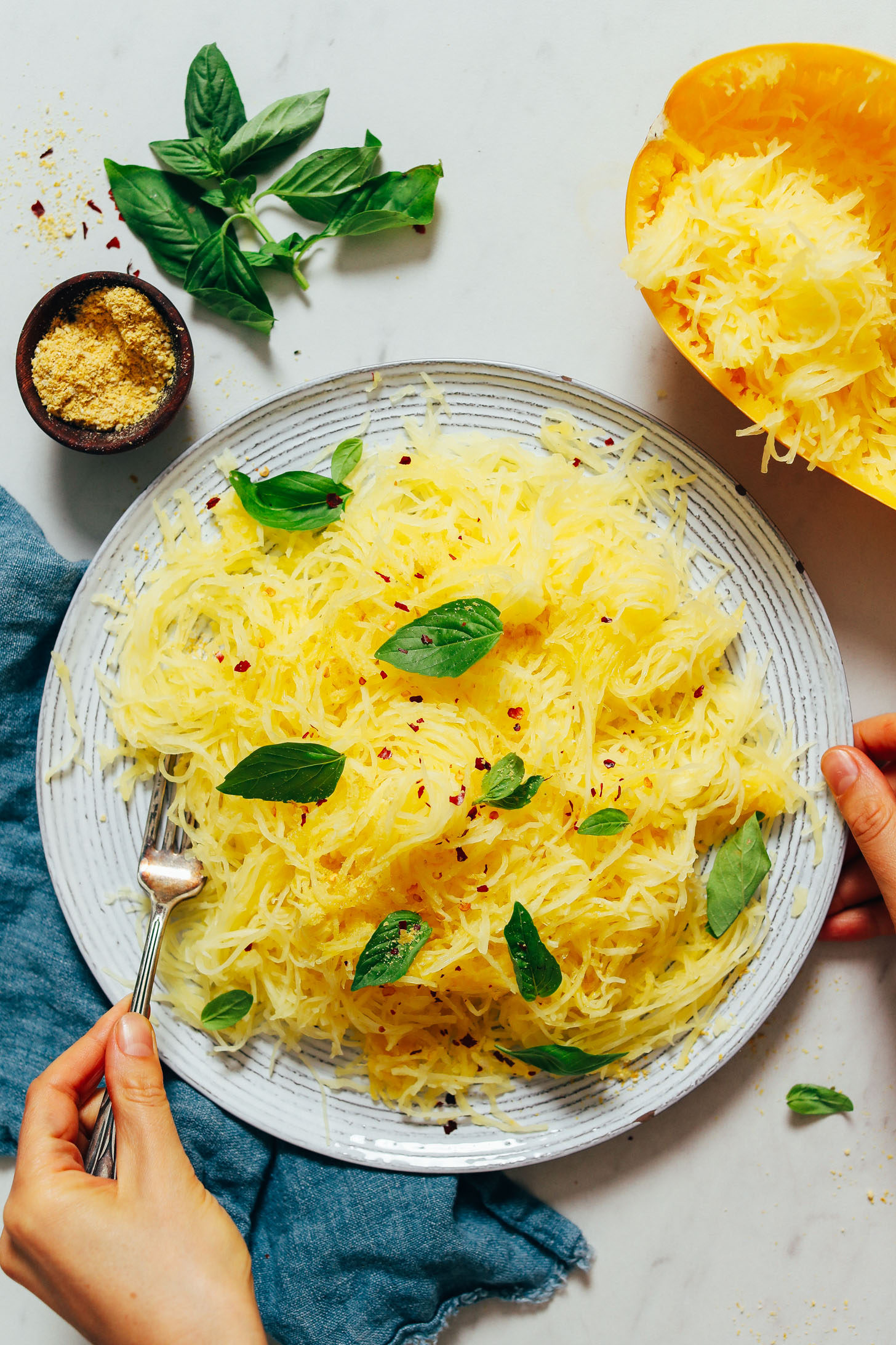 Bowl of spaghetti squash topped with fresh basil and red chili flakes