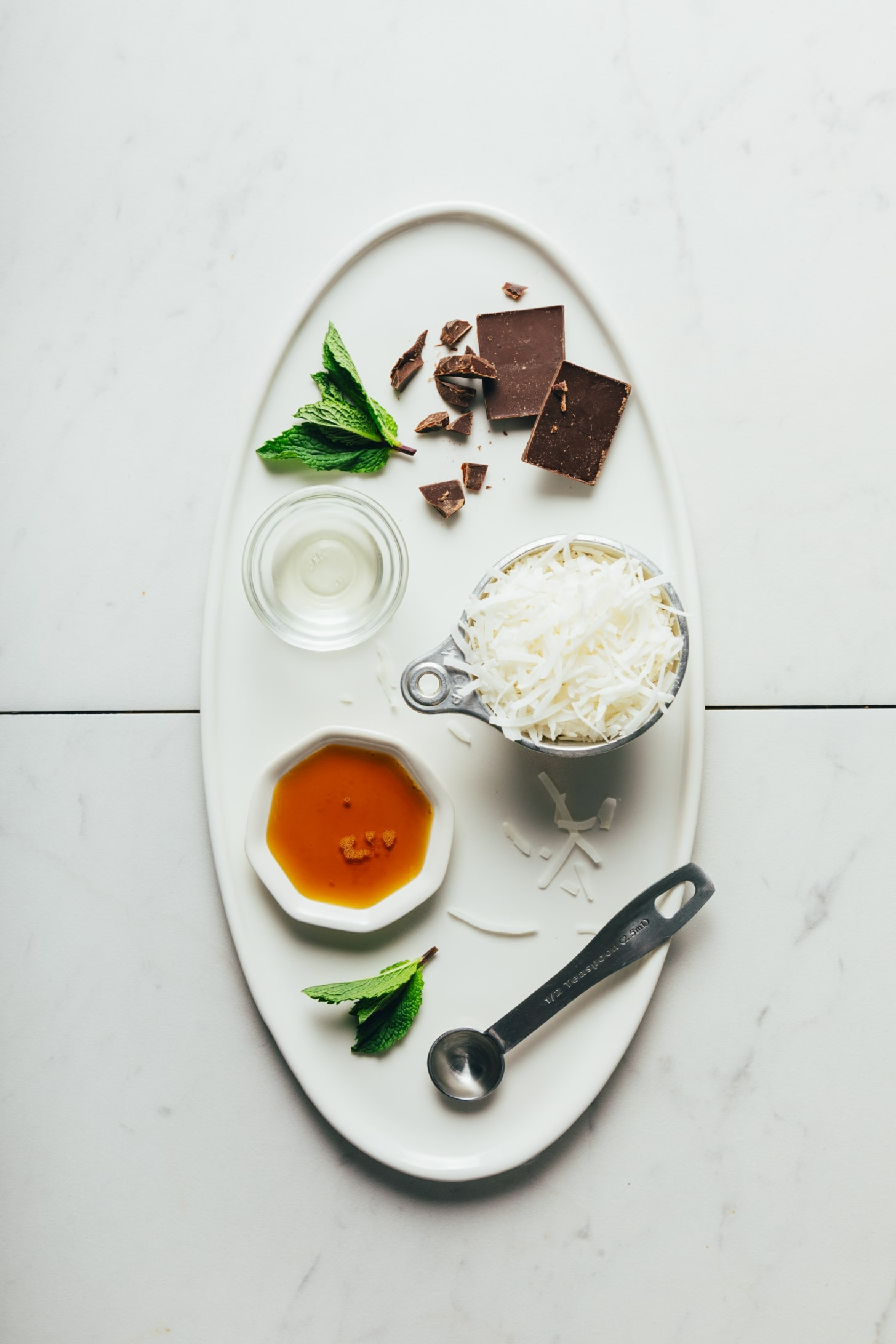 Tray of dark chocolate, shredded coconut, coconut oil, maple syrup, and fresh mint