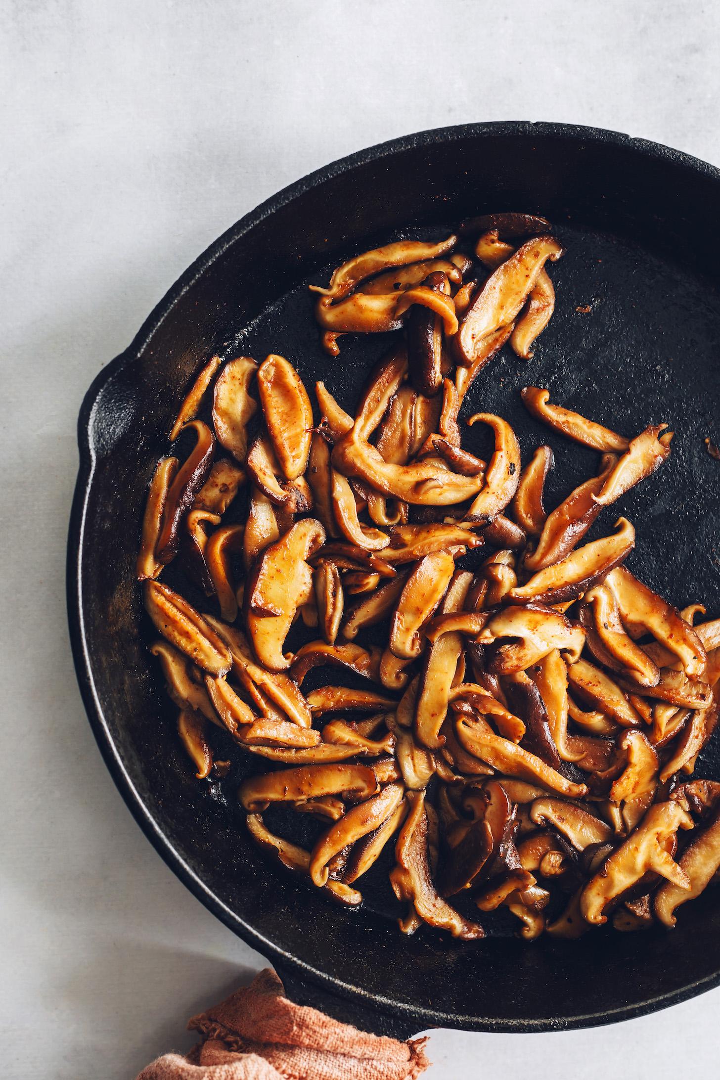 Sliced shiitake mushrooms in a cast iron skillet coated in seasonings