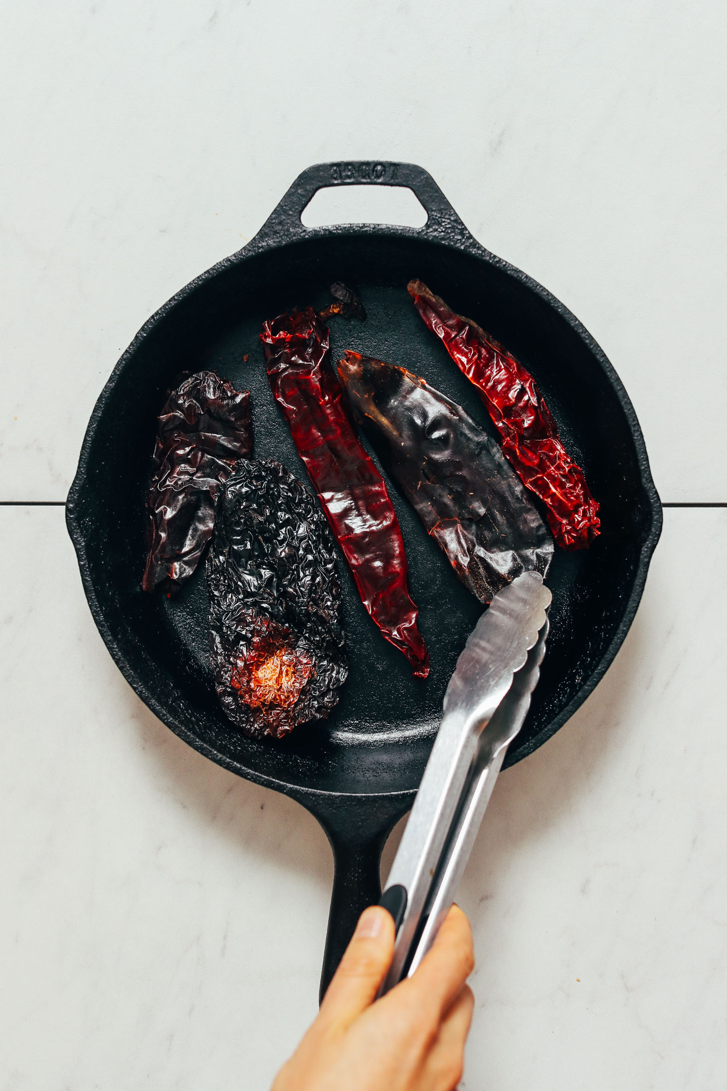 Toasting dried chilies in a cast iron skillet