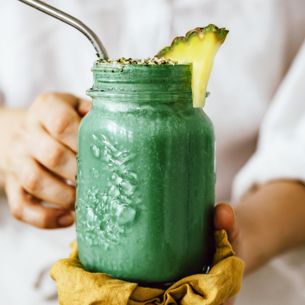 Holding a glass jar filled with our green lemonade smoothie recipe