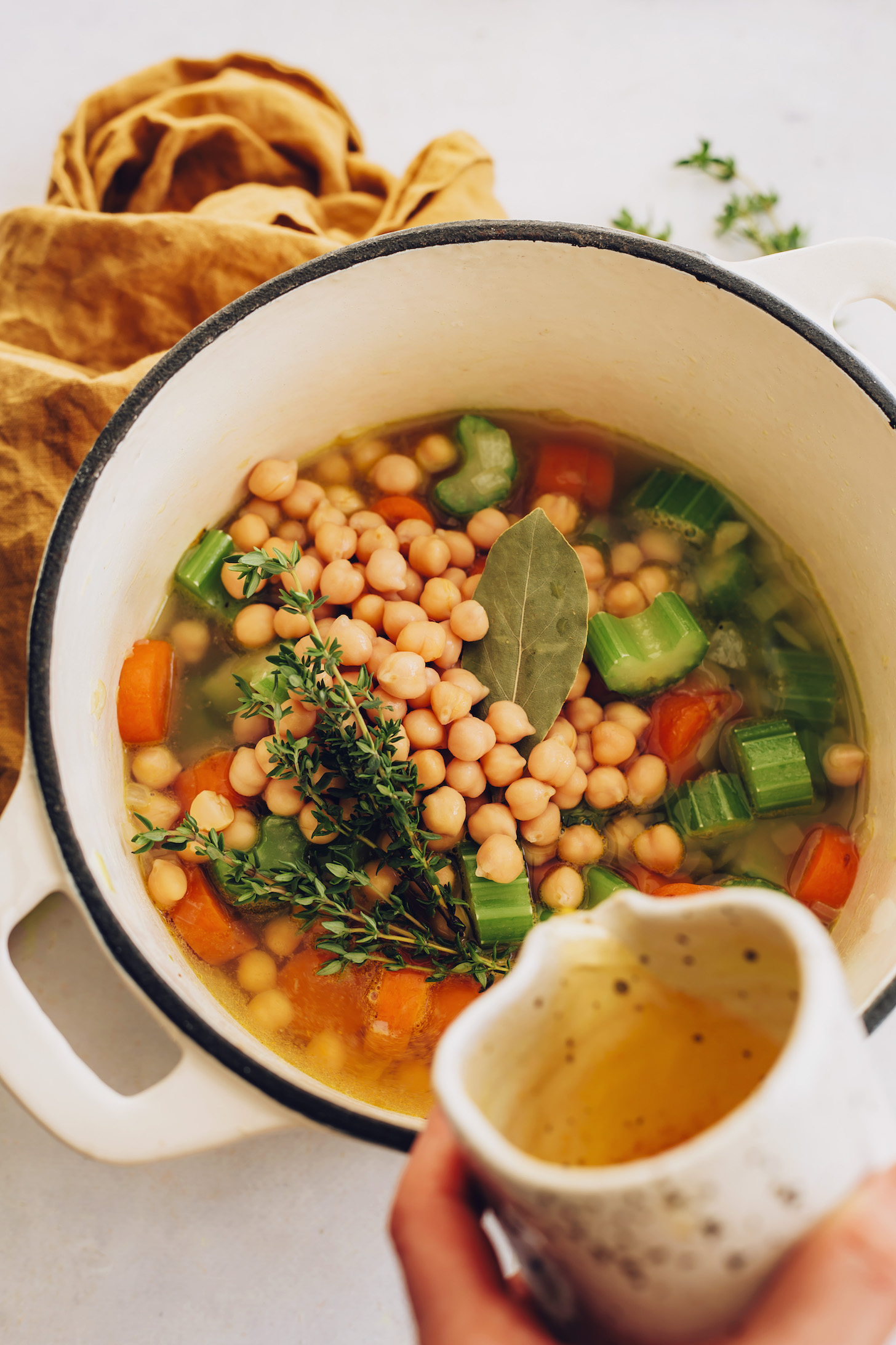 Pouring vegetable broth over carrots, celery, thyme, chickpeas, and a bay leaf