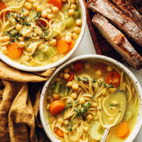 Bowls of vegan chicken noodle soup made with chickpeas