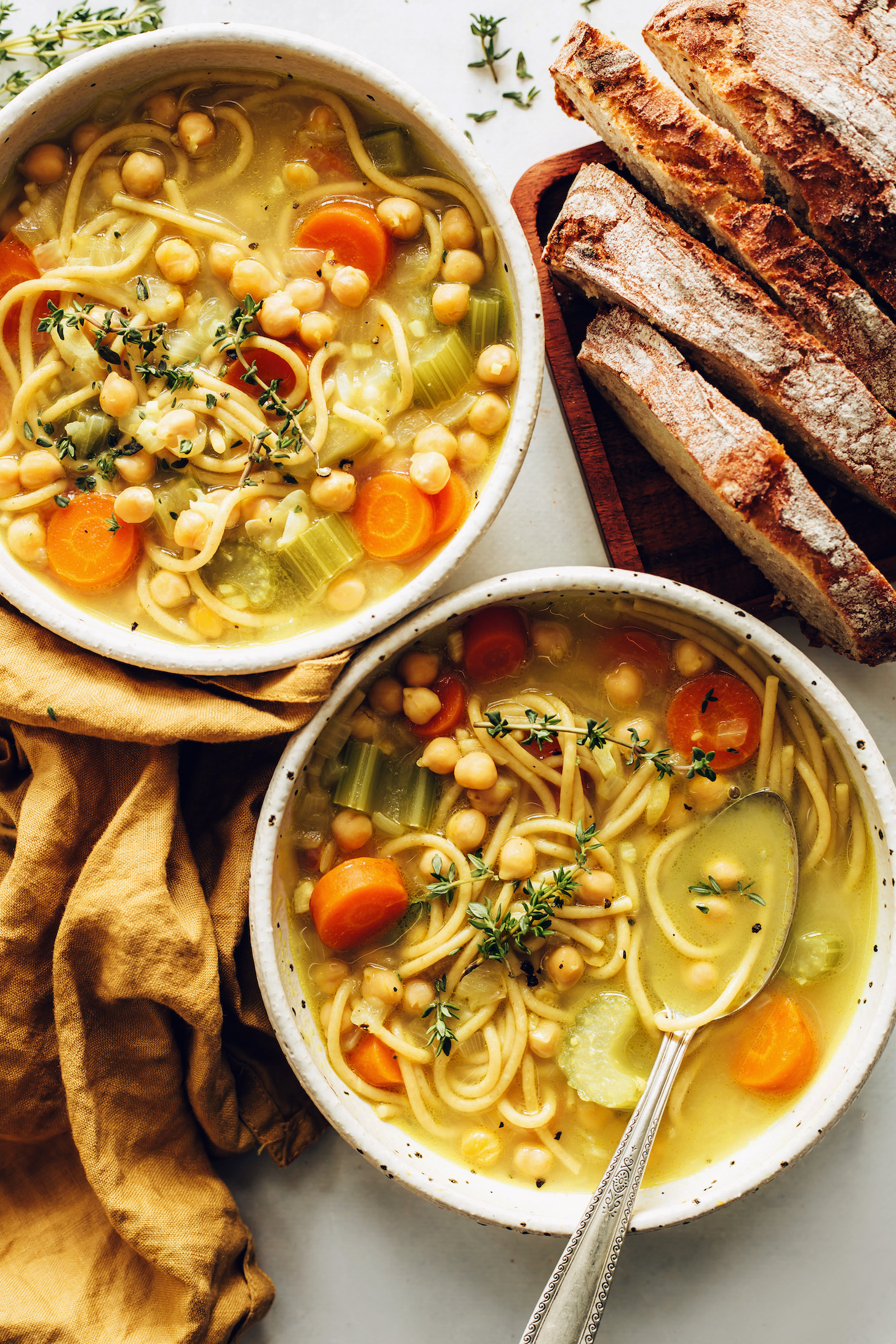 Sliced sourdough bread next to two bowls of chickpea noodle soup