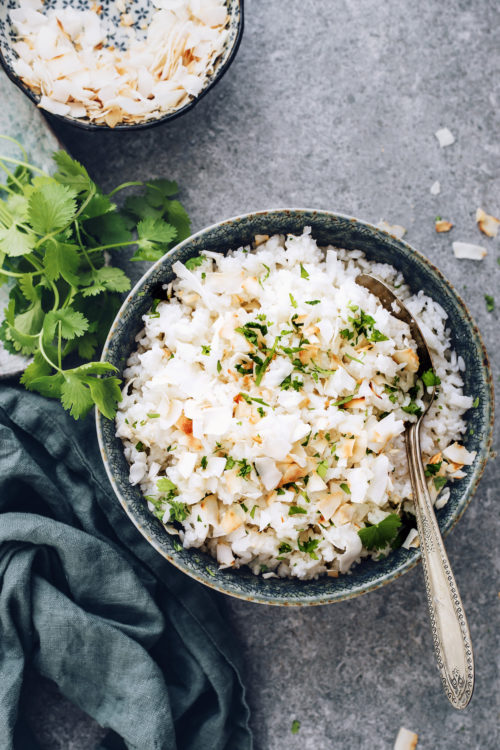 Bowl of easy coconut rice topped with cilantro and toasted coconut flakes