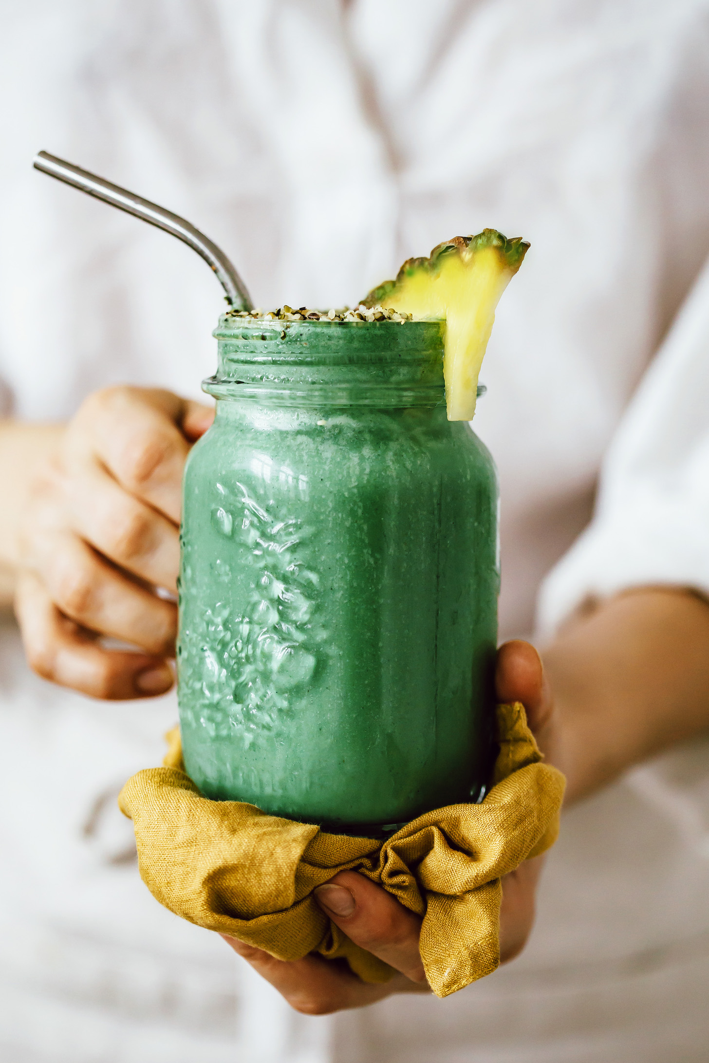 Holding a glass jar of our tropical green smoothie