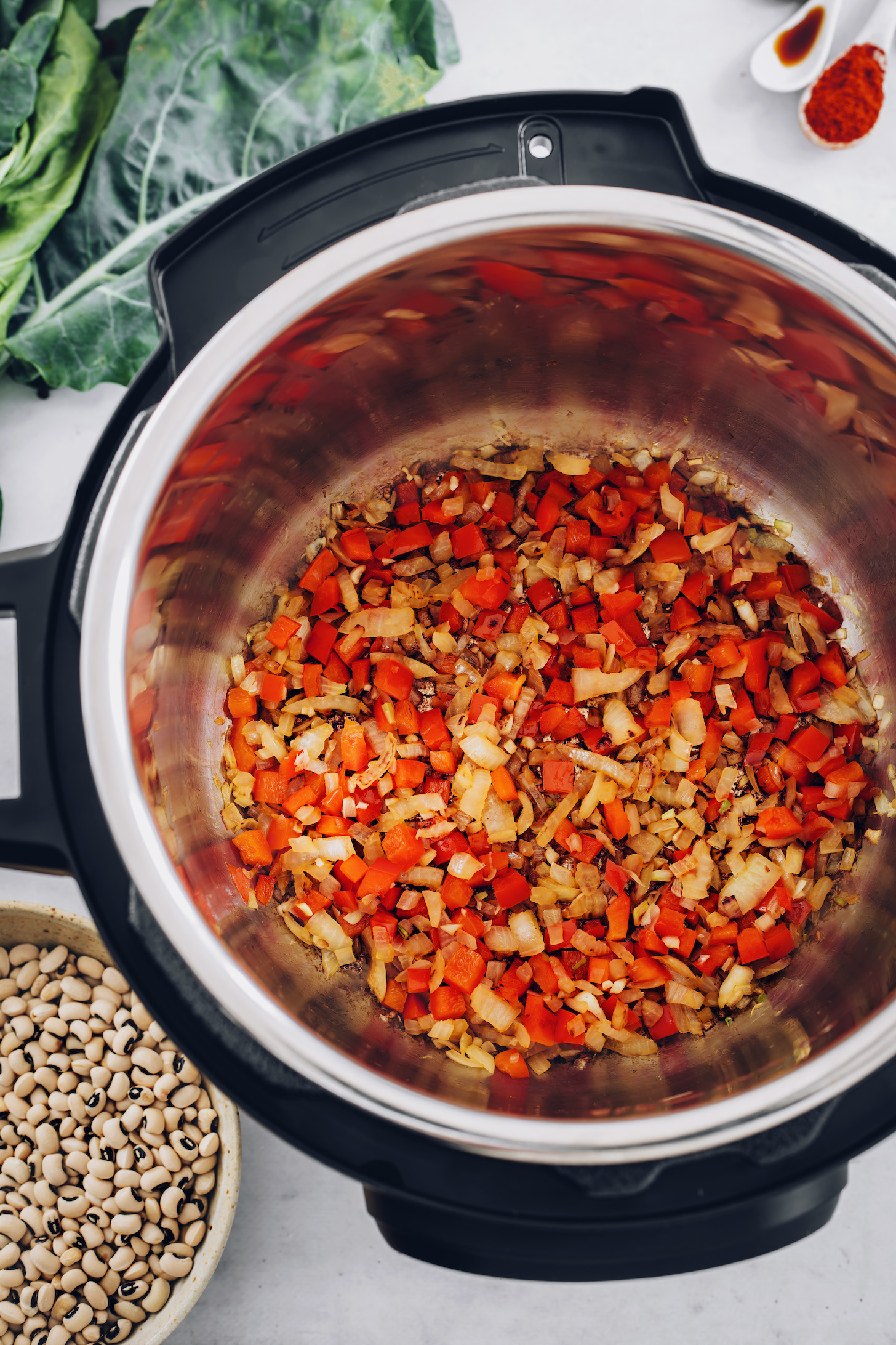 Bowl of black eyed peas next to an Instant Pot of sautéed onion and bell pepper