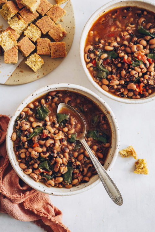 Two bowls of Instant Pot Black Eyed Peas and Greens with vegan cornbread