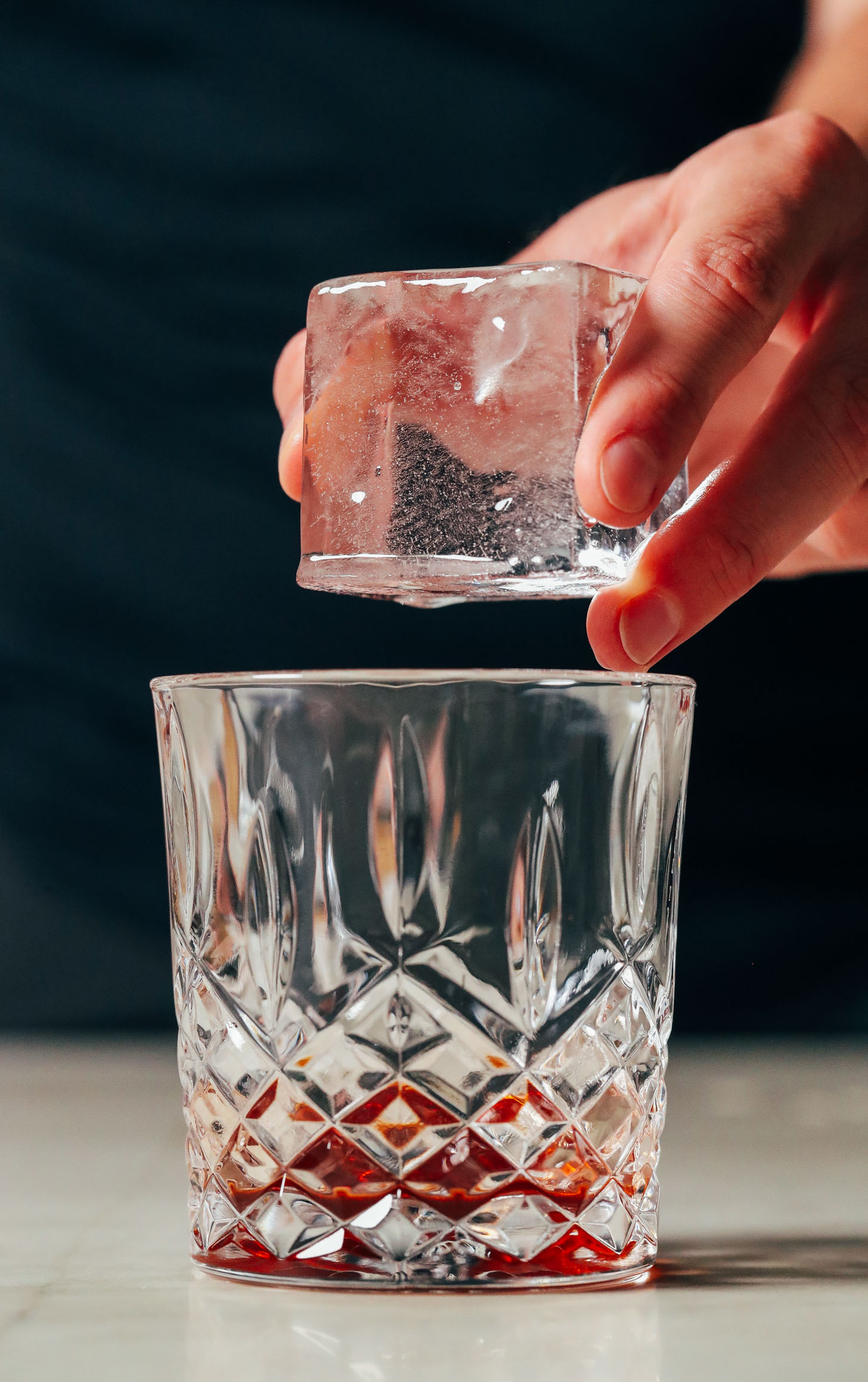 Adding a clear ice cube to a glass of bitters