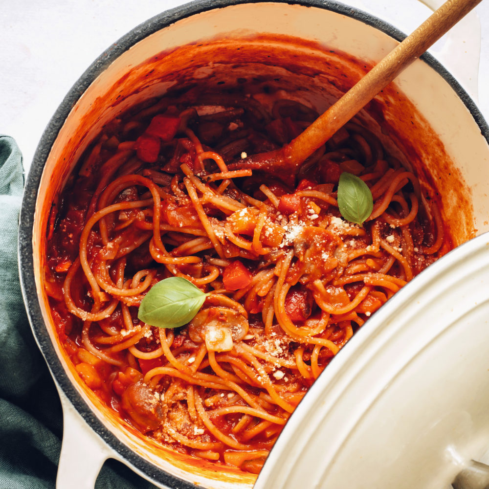 Big pot of vegan spaghetti topped with fresh basil