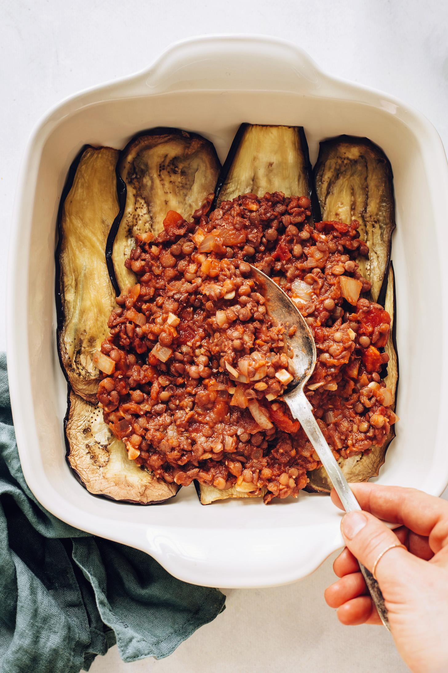 Pouring lentil filling over baked eggplant slices