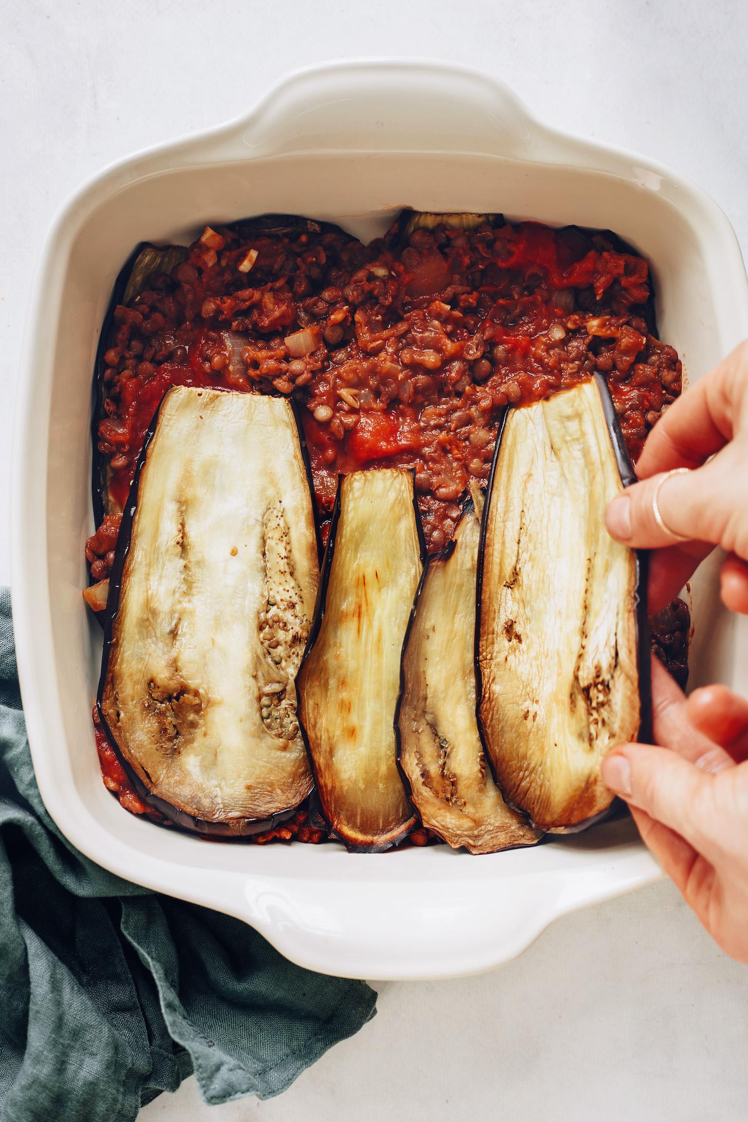 Adding eggplant slices over a lentil tomato filling