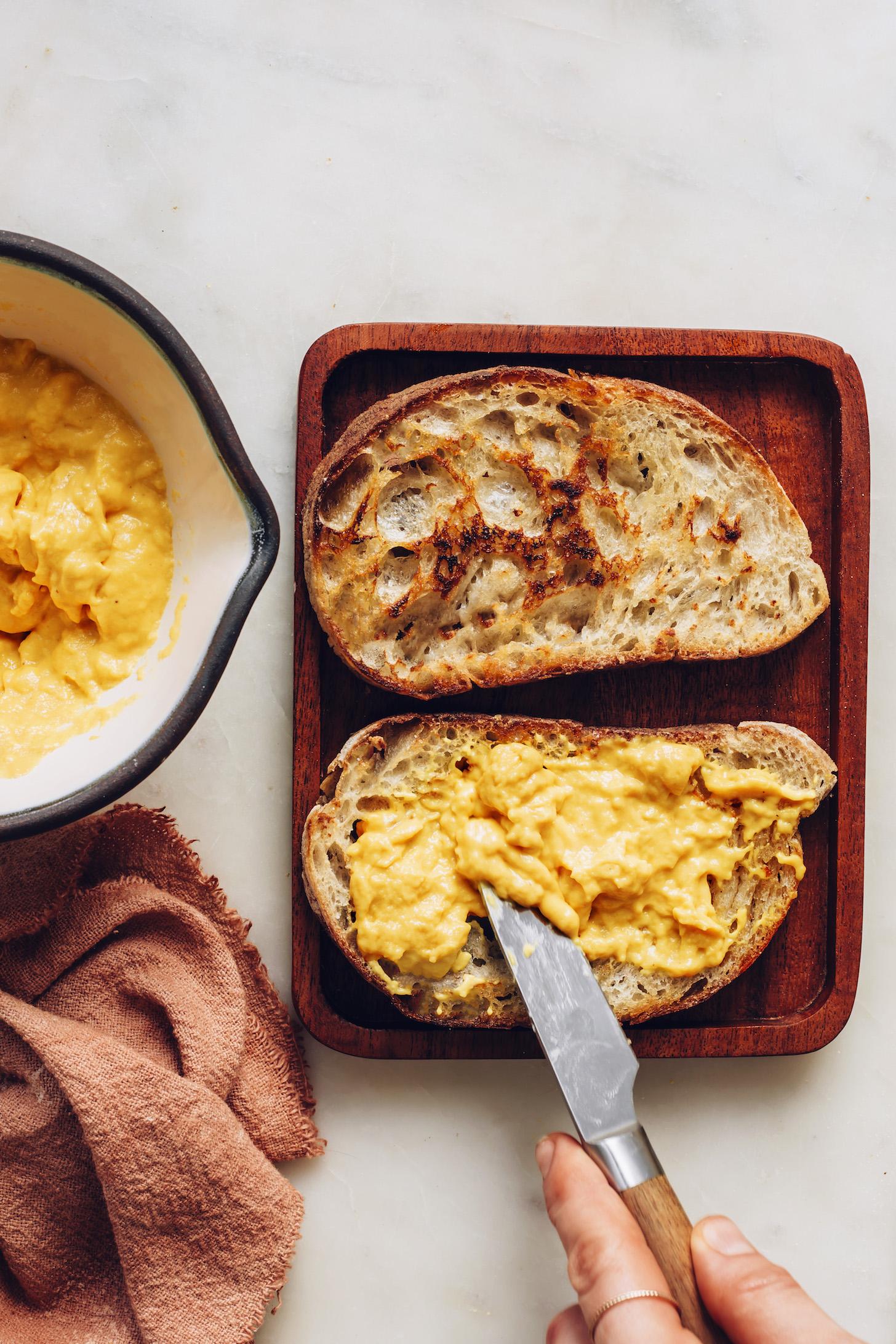 Spreading vegan cheddar cheese onto sourdough bread