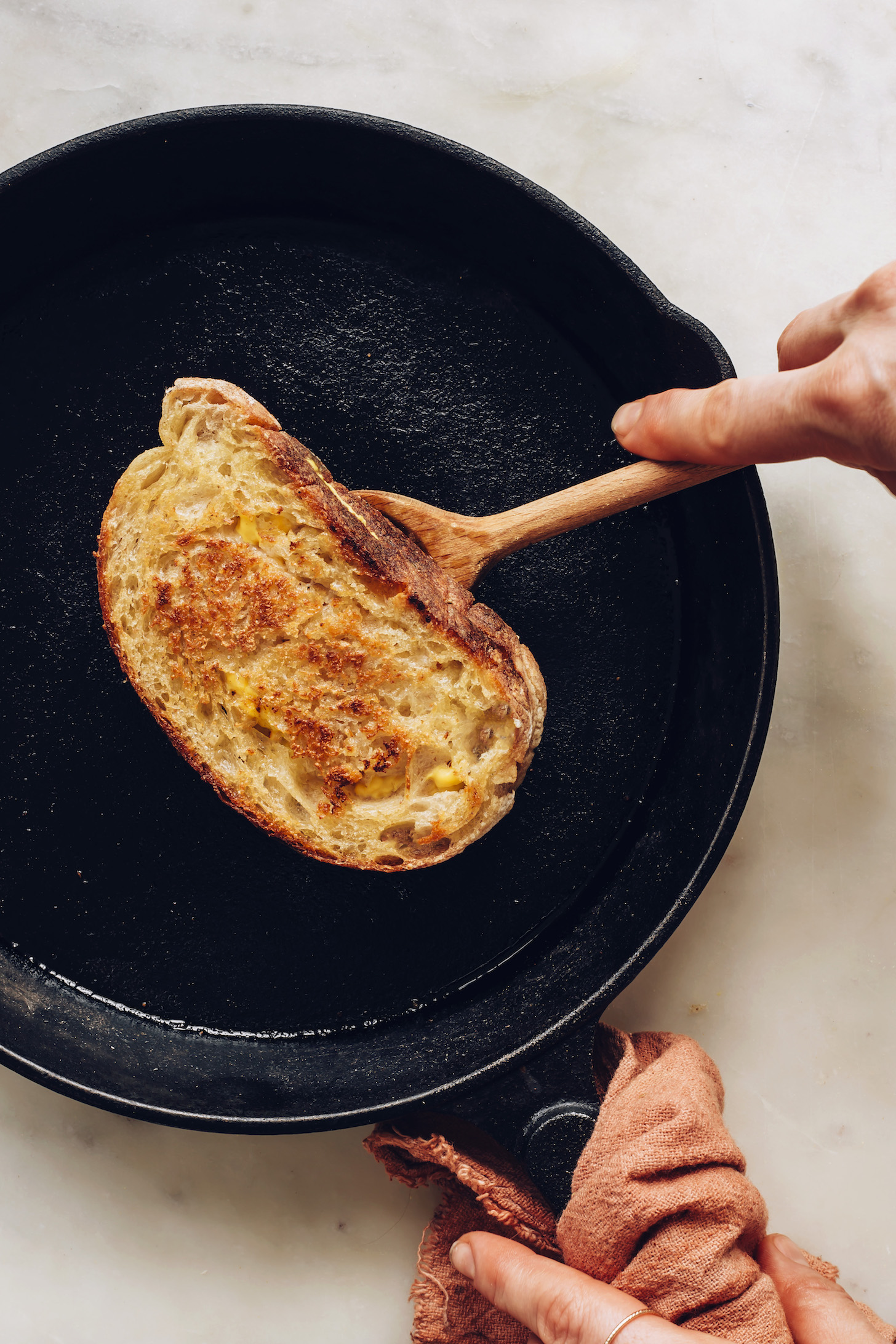 Using a wooden spoon to flip a vegan grilled cheese in a cast iron pan