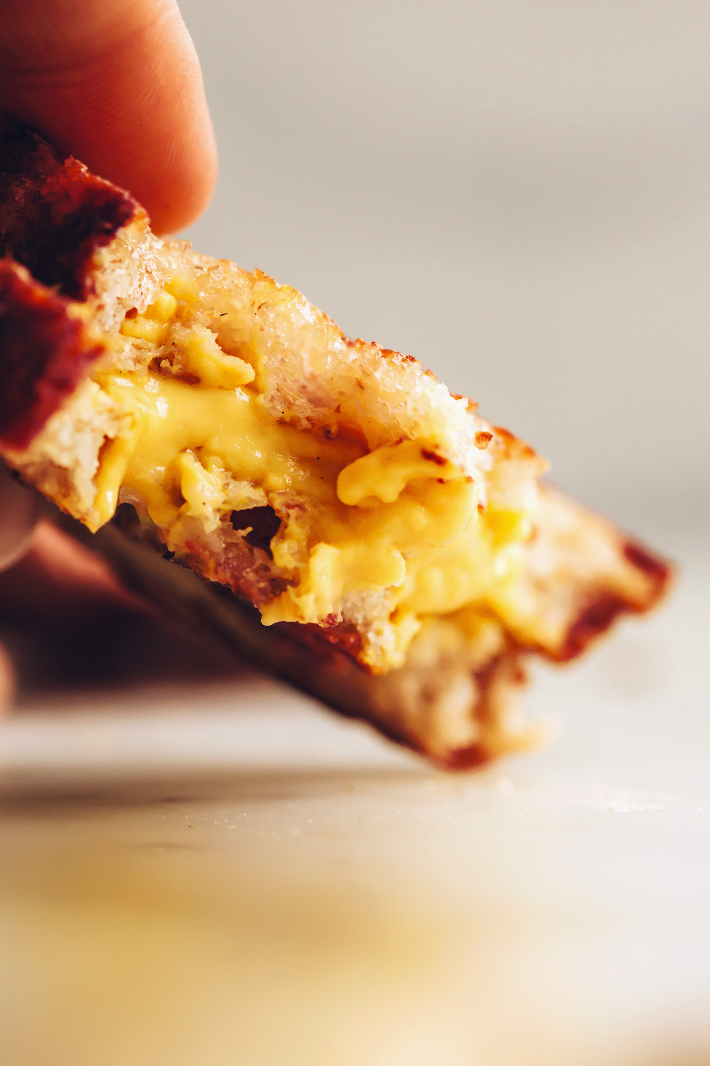 Close up shot of the melty cheddar cheese in our vegan grilled cheese sandwich