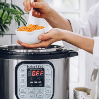 Holding a bowl of red lentils over an Instant Pot