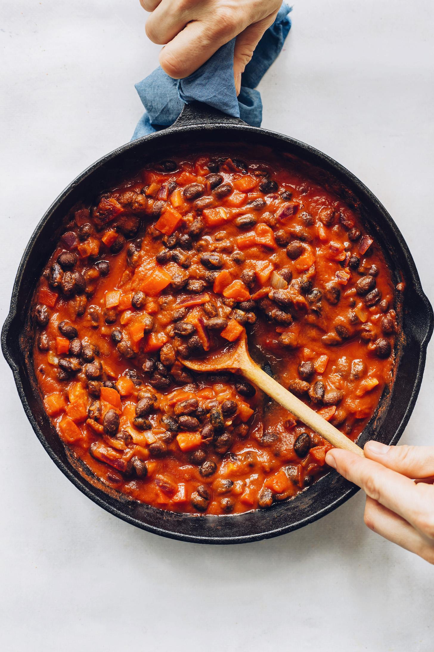 Revuelva una sartén con frijoles negros, cebolla, pimiento y salsa de enchilada
