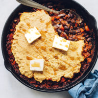Cast iron skillet filled with Cornbread & Black Bean Enchilada Bake