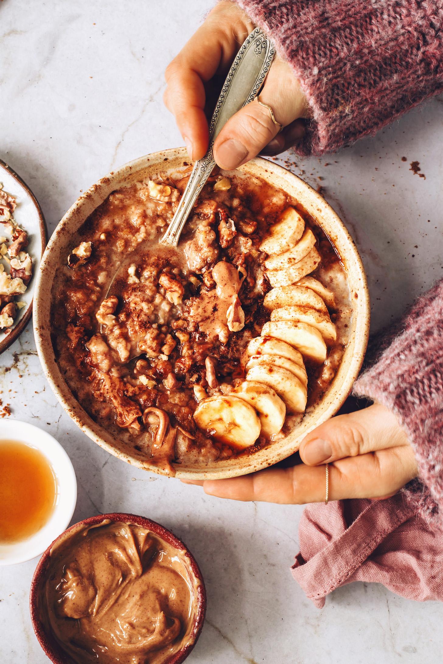 Ореховое масло, грецкие орехи и кленовый сироп рядом с миской бананового хлеба с овсяными хлопьями