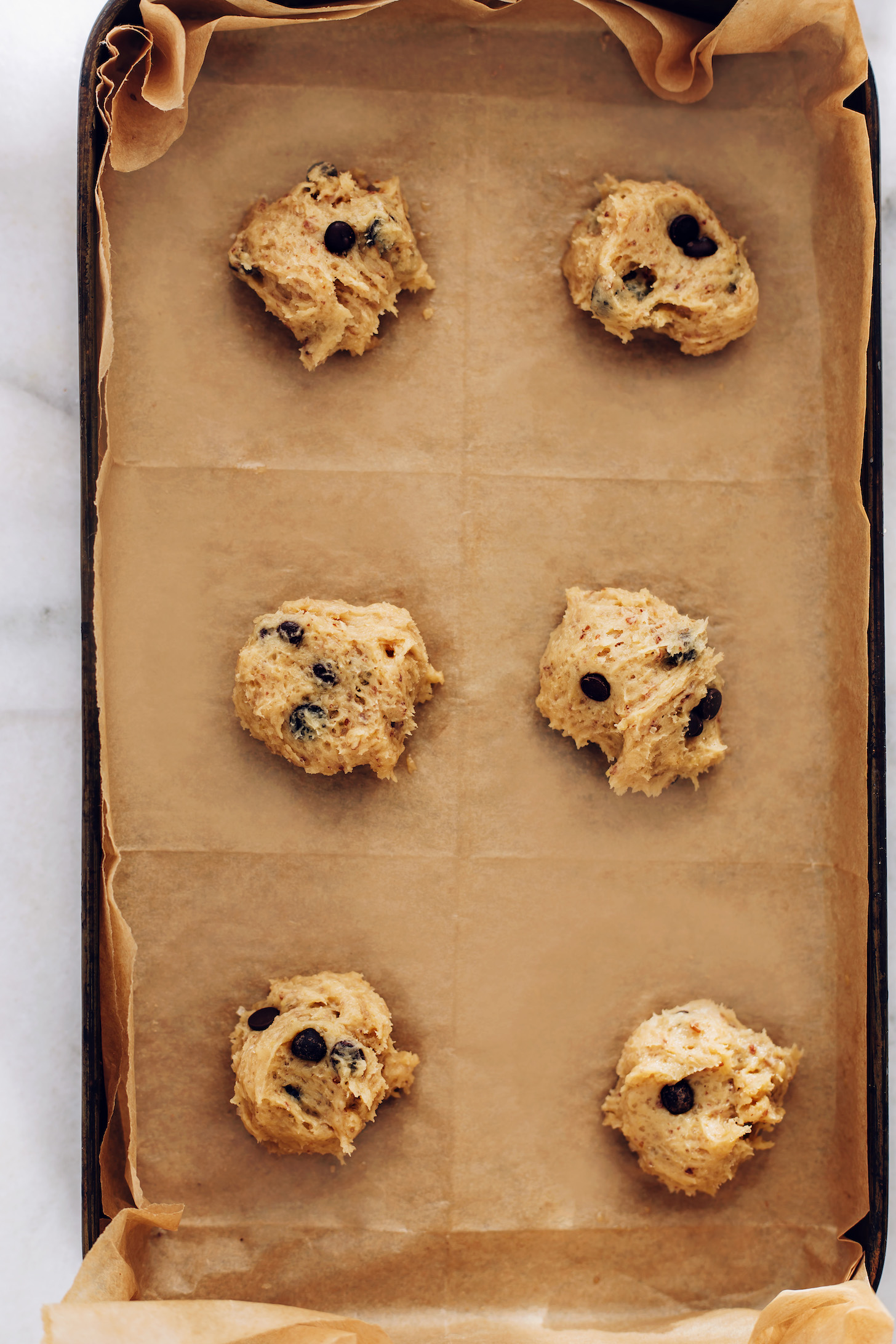 Balls of chocolate chip cookie dough on a parchment-lined baking sheet