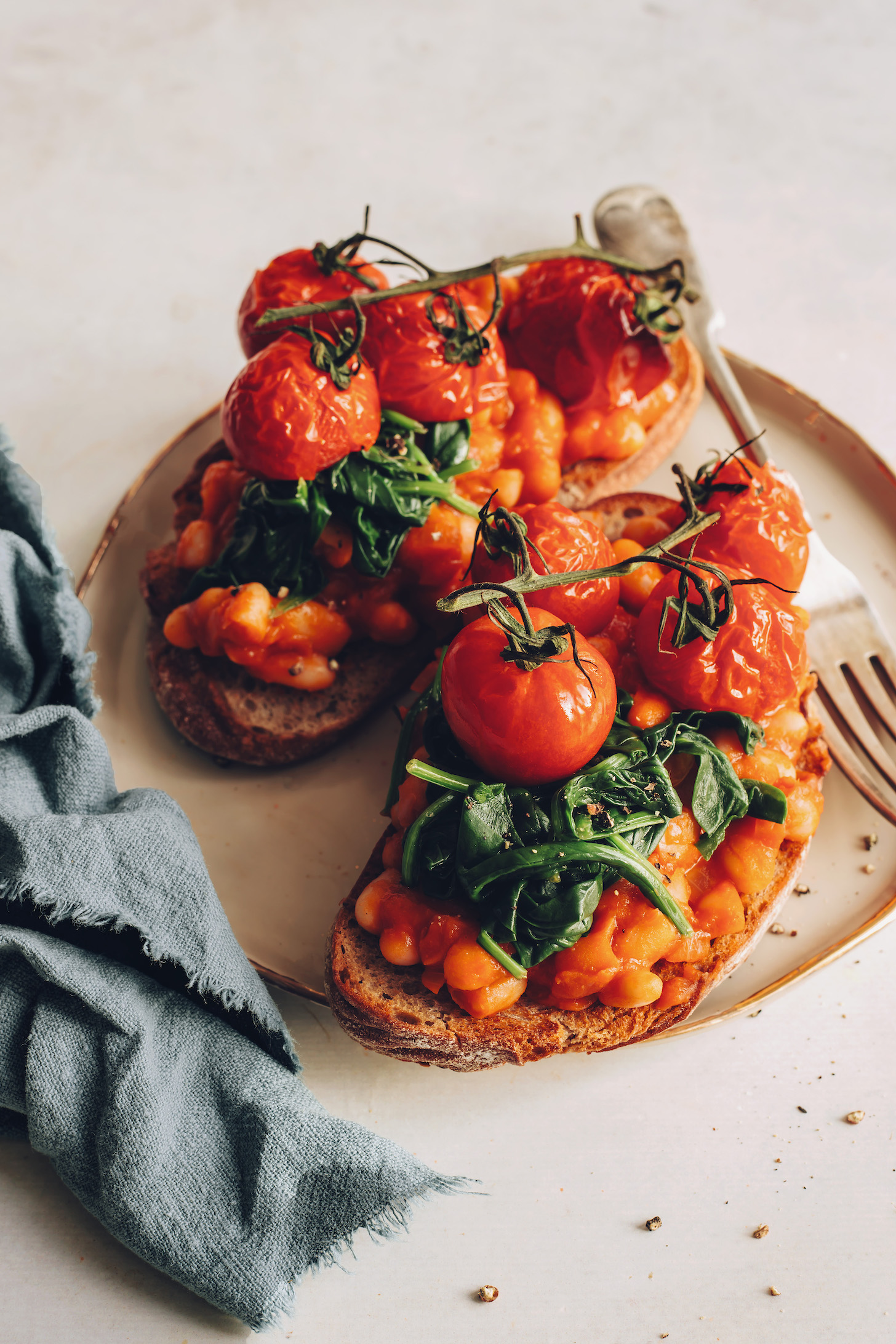 Slices of sourdough bread topped with British baked beans, wilted spinach, and slow roasted tomatoes