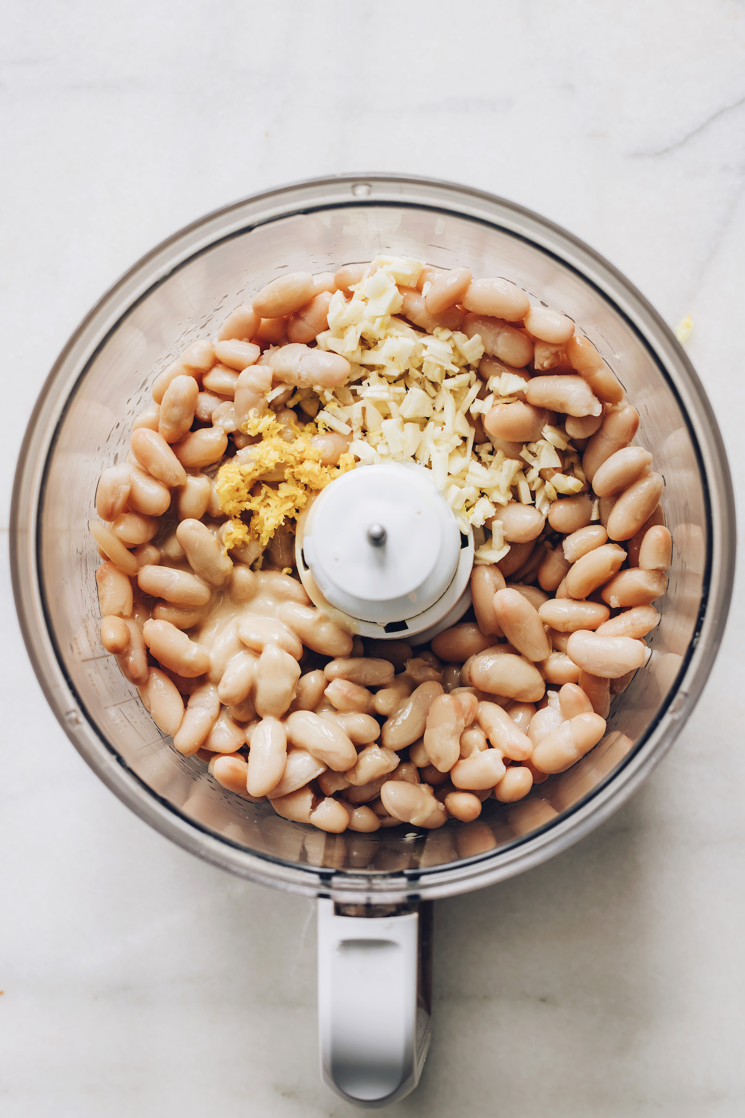 Food processor with white beans, garlic, and lemon zest