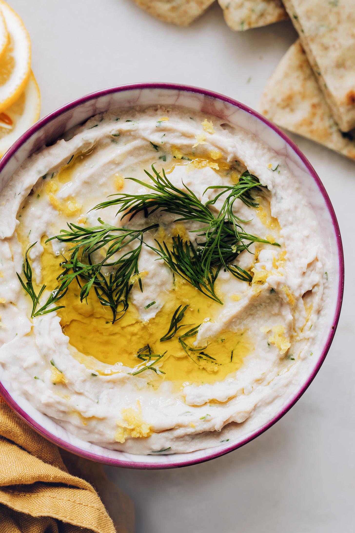 Чаша хумуса из белой фасоли, заправленная свежим укропом и оливковым маслом