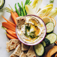 Bowl of white bean hummus surrounded by pita bread and fresh vegetables for dipping