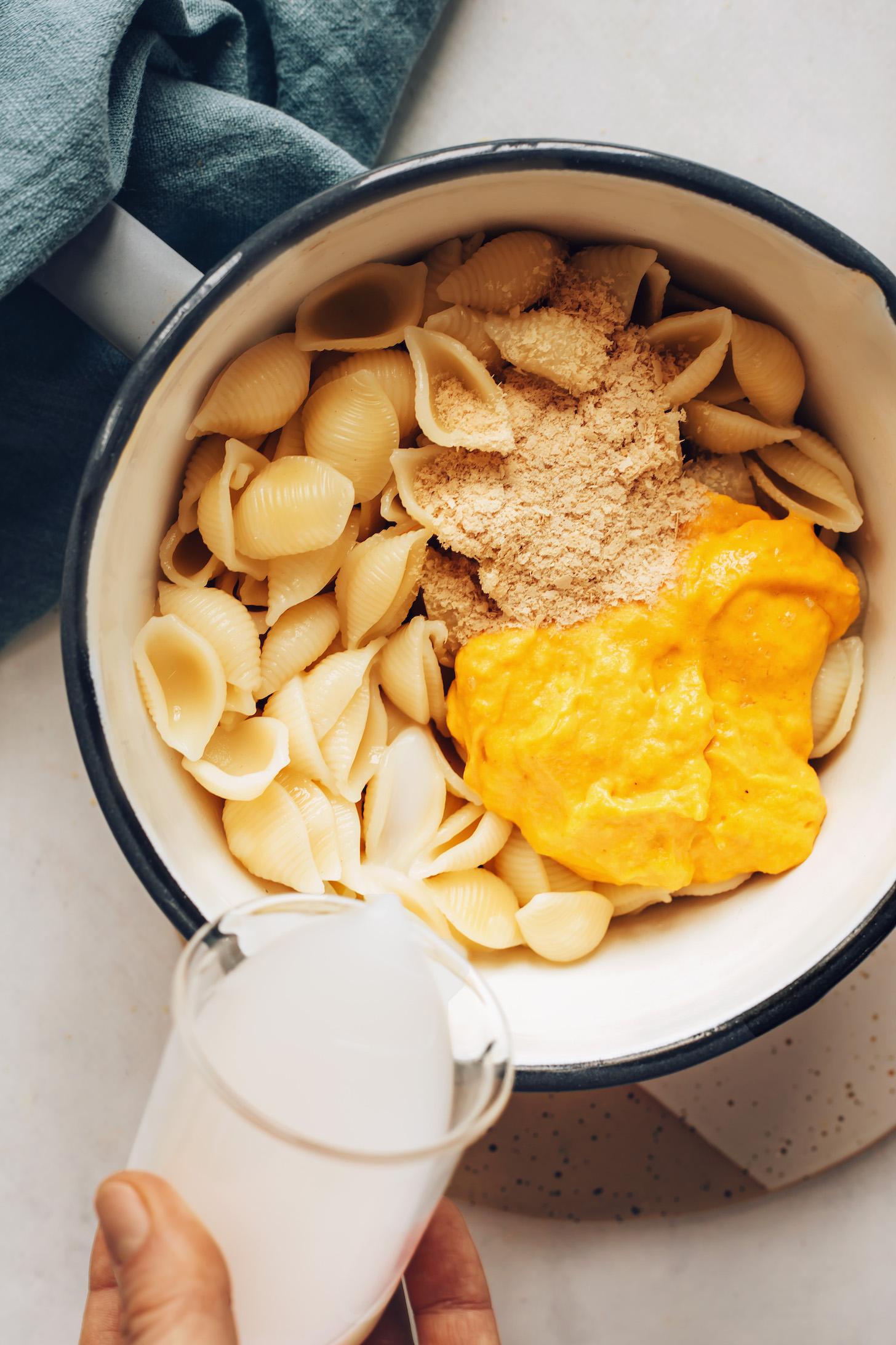 Verser le lait d'amande dans une casserole de pâtes sans gluten, de levure nutritionnelle et de fromage cheddar végétalien