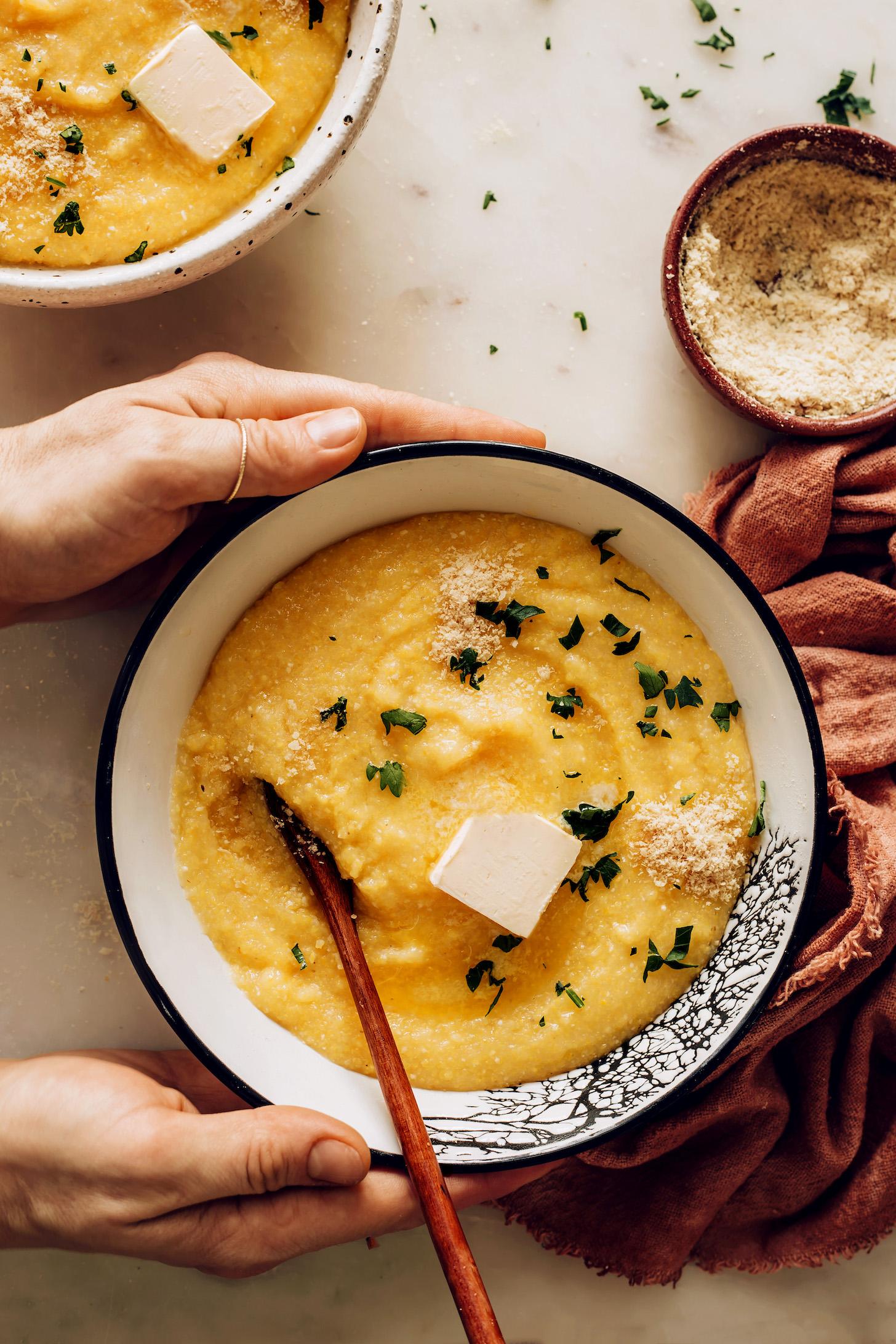 Bowl of vegan polenta with fresh herbs and vegan parmesan