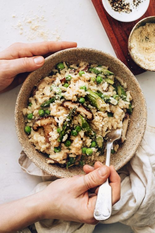 Holding a fork in a bowl of vegan risotto with spring vegetables
