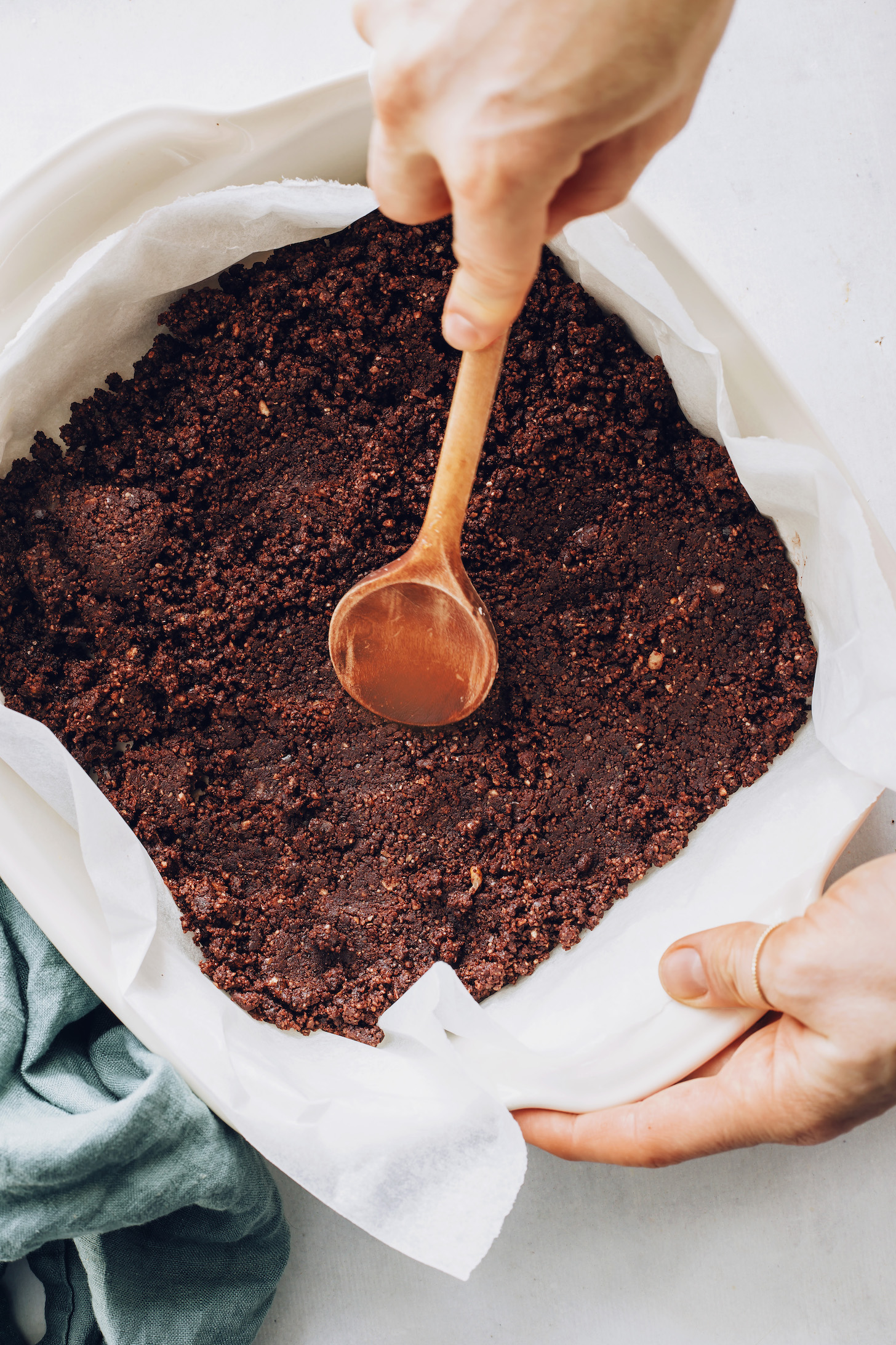 Using a wooden spoon to spread the chocolate brownie layer in a parchment-lined pan