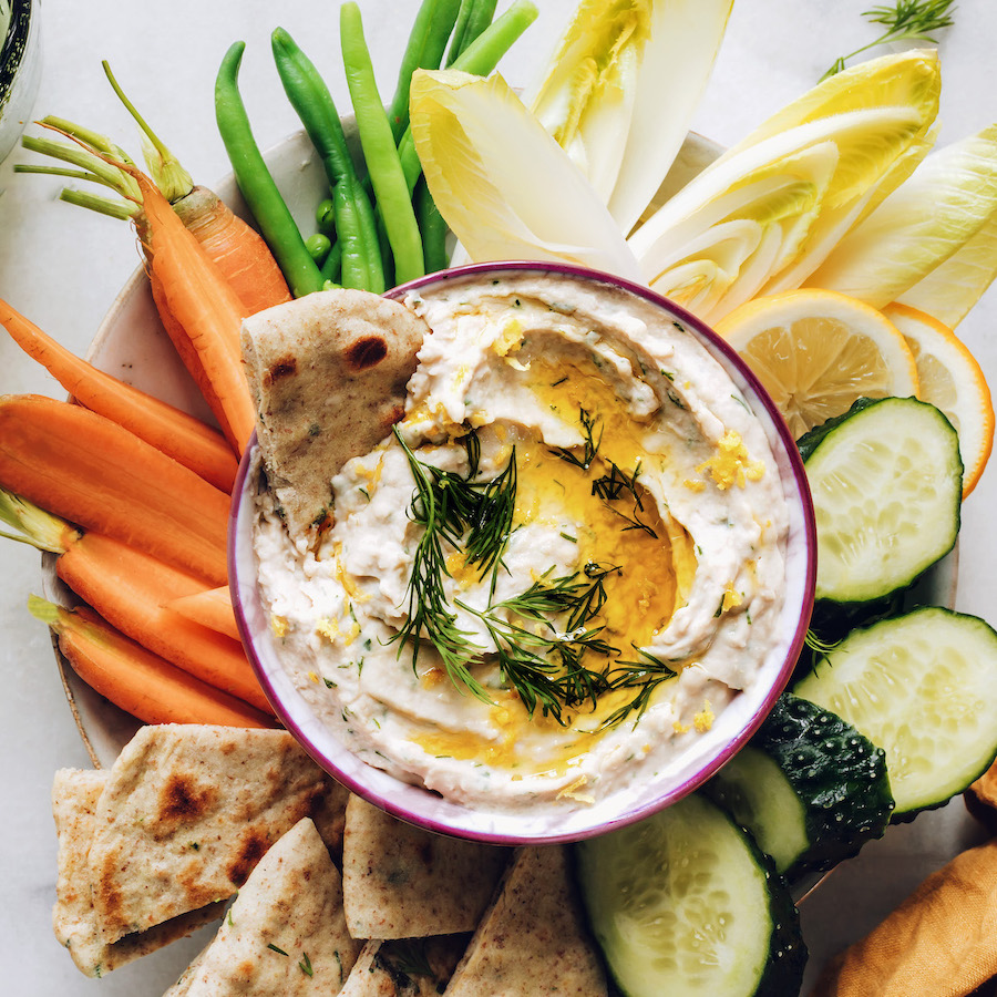 Bowl of white bean hummus surrounded by fresh vegetables and pita bread