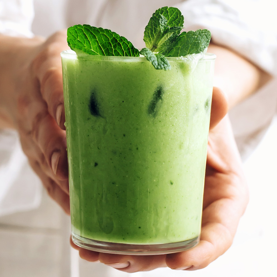 Hands holding a glass of our iced matcha latte topped with fresh mint leaves
