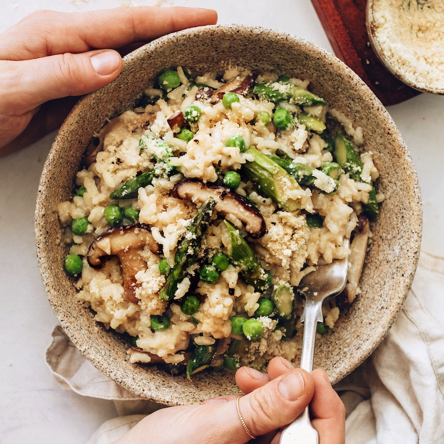 Bowl of vegan risotto with miso, spring vegetables, and vegan parmesan
