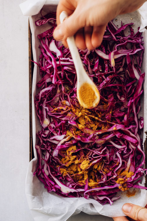 Sprinkling curry powder over a pan of thinly sliced cabbage