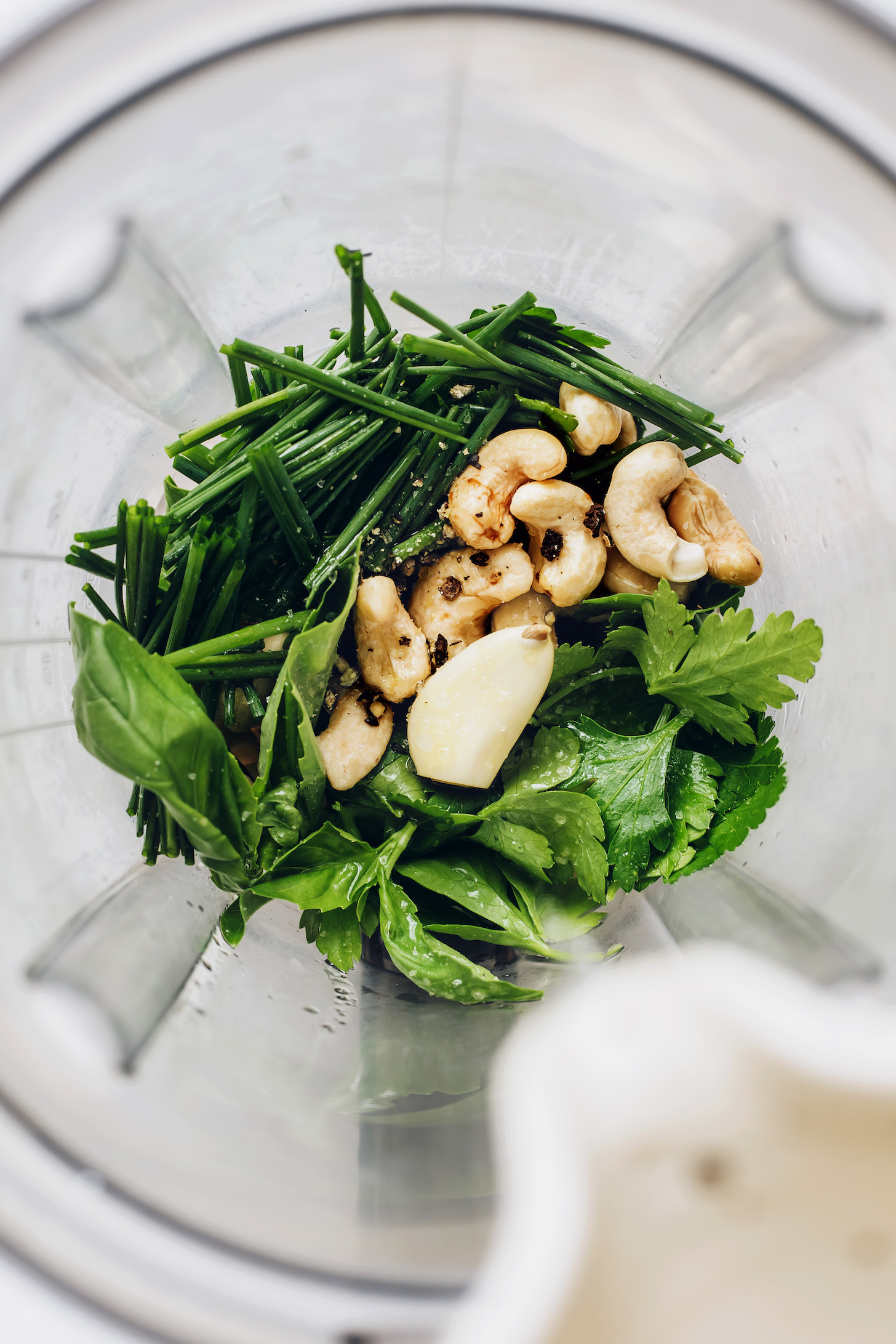 Blender with fresh herbs, cashews, garlic, and black pepper