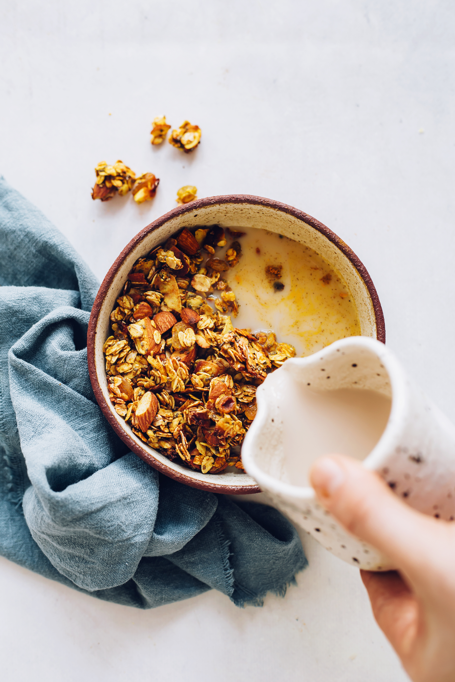 Pouring dairy-free milk into a bowl of golden milk granola