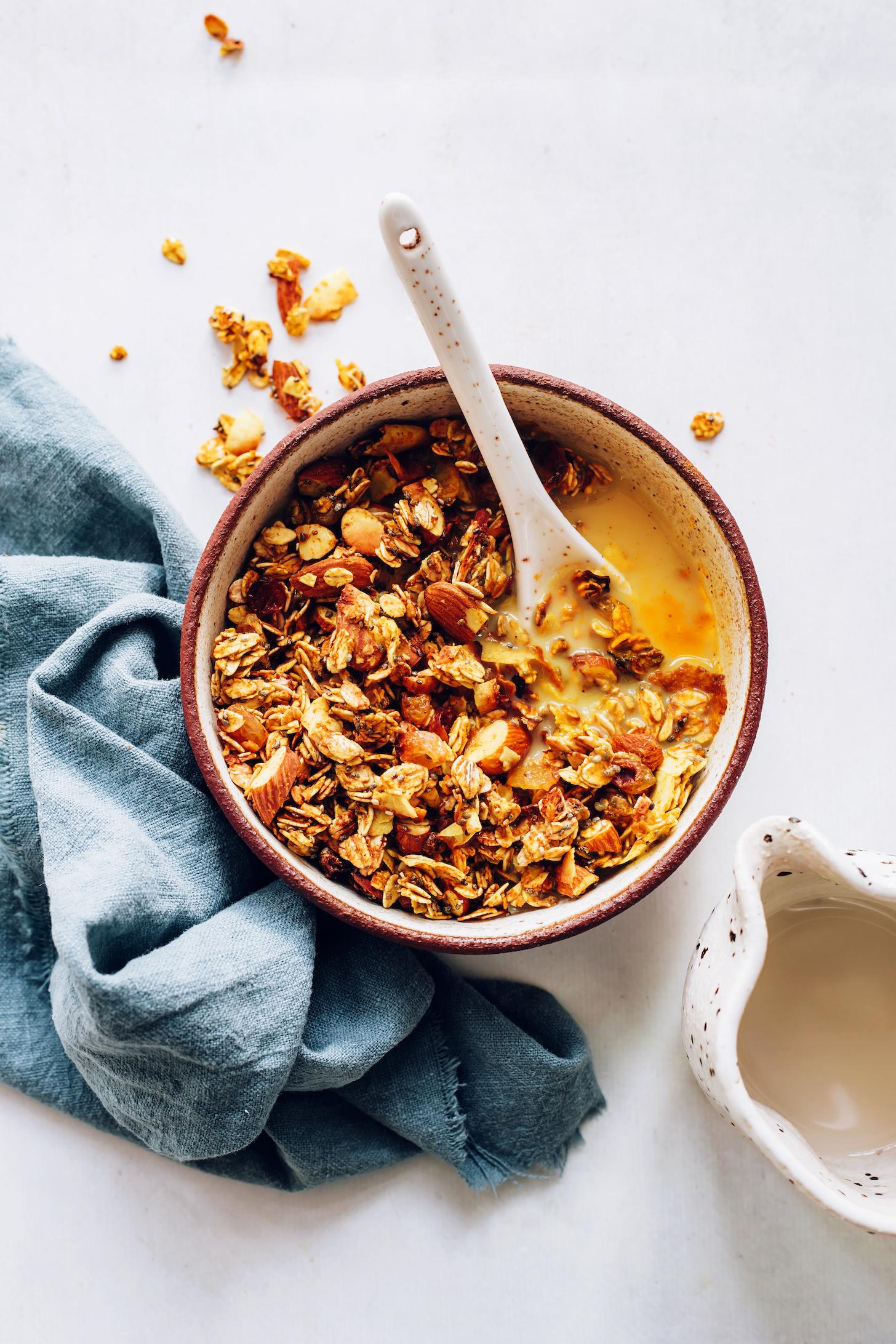 Spoon in a bowl of golden milk granola