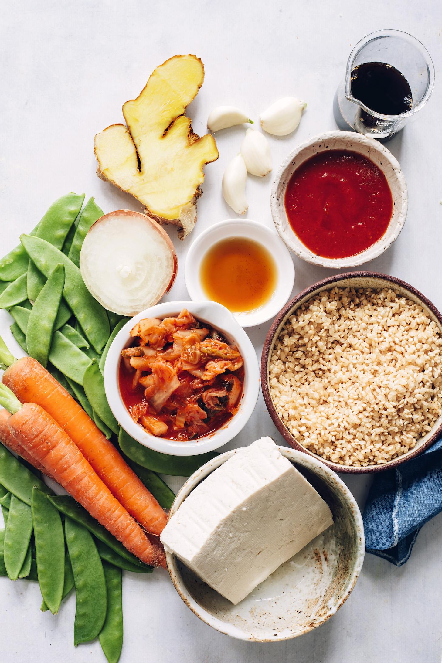 Zanahorias, guisantes, tofu, kimchi, arroz, cebolla, ajo, jengibre, aceite de sésamo tostado, gochujang y tamari
