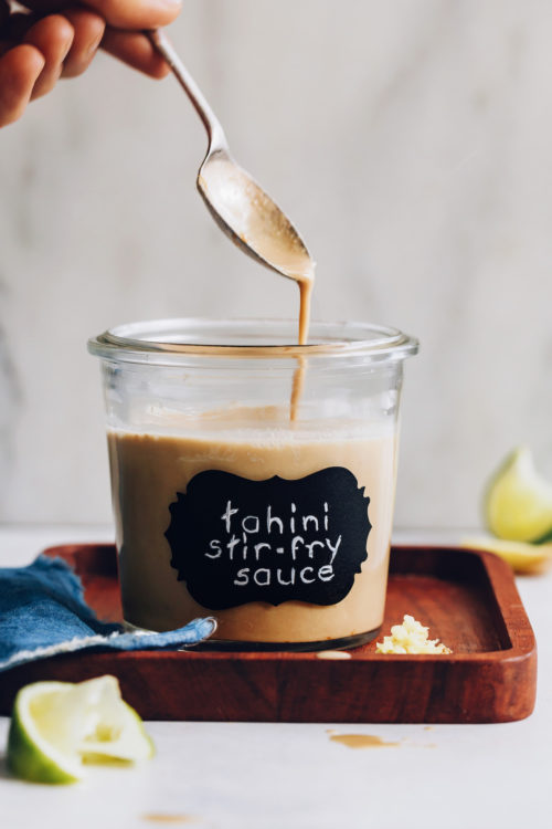 Tahini stir fry sauce dripping from a spoon into a jar
