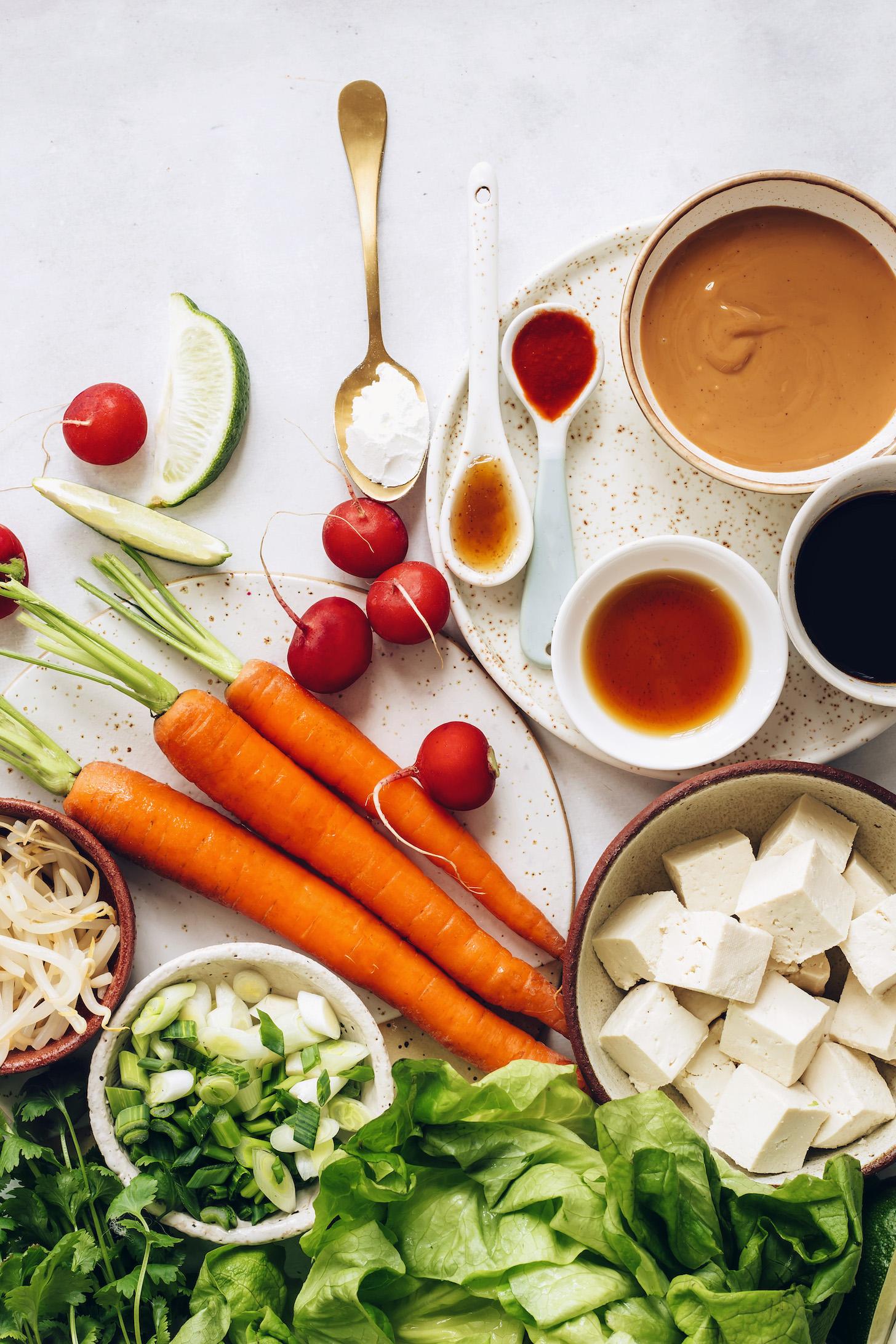Carrots, radish, green onion, bean sprouts, lettuce, tofu, cornstarch, peanut butter, chili garlic sauce, maple syrup, toasted sesame oil, and tamari
