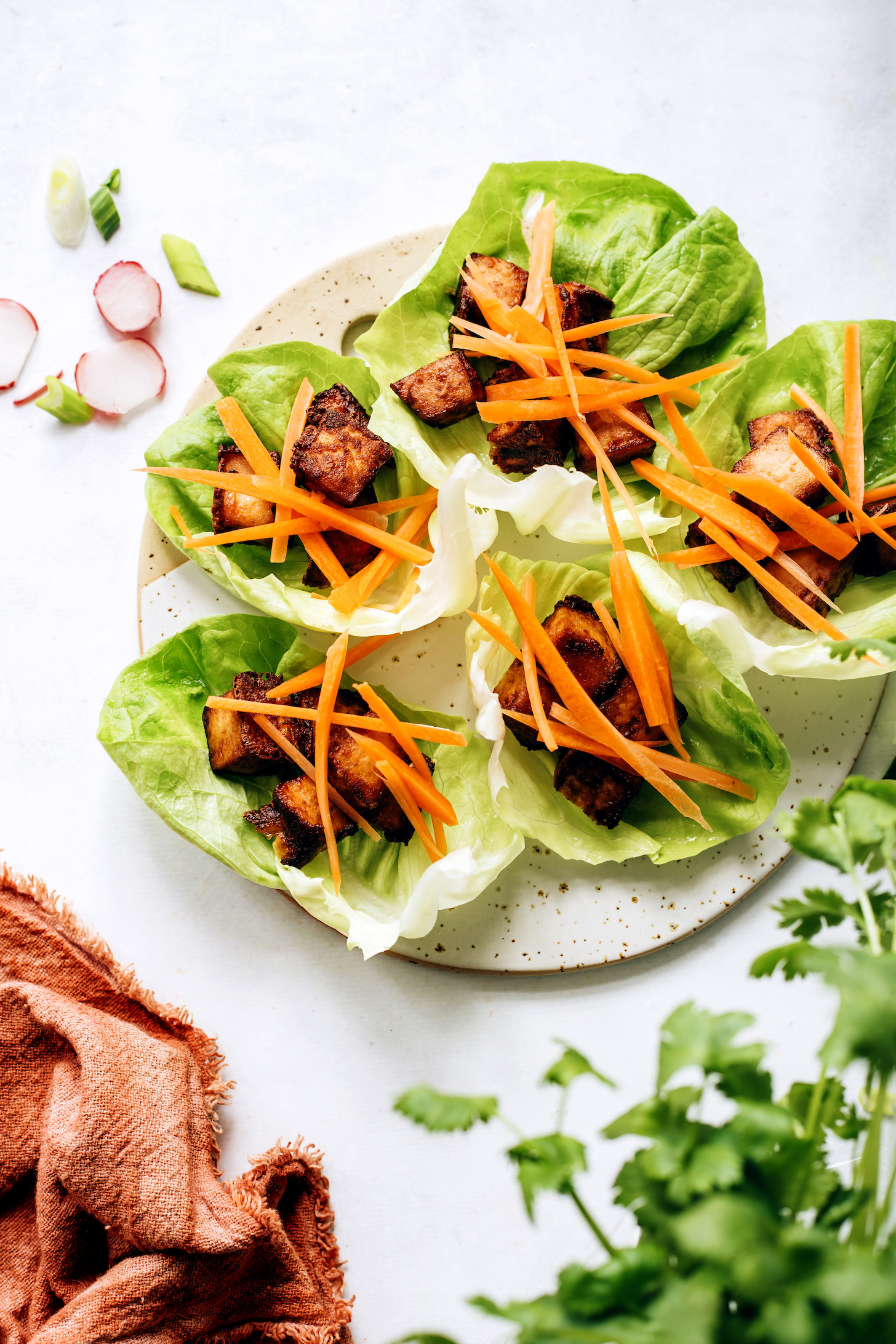 Lettuce leaves topped with crispy tofu and sliced carrots