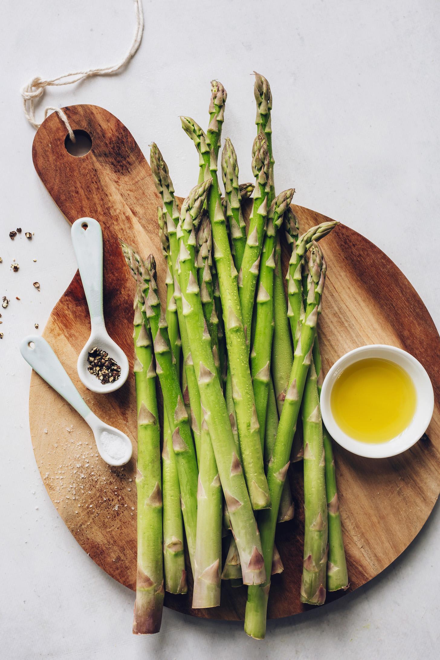 Tabla de cortar de espárragos, aceite de oliva, sal y pimienta